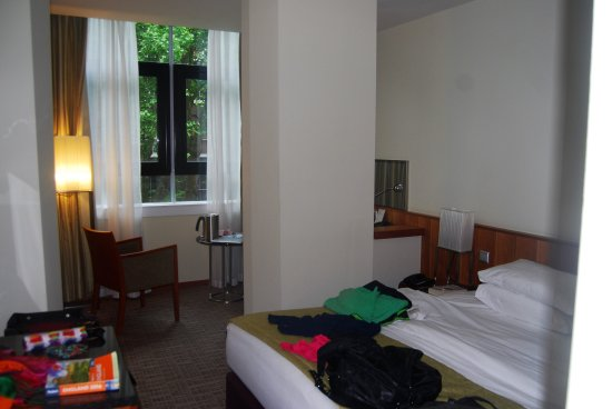 K+K Hotel George: My messy room. King sized bed. large windows. Nook with desk, small table and chairs.