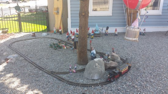 "Fireside Inn: The electric train set in the front yard. Note the ""Godzilla"" figurine just left of the train!"
