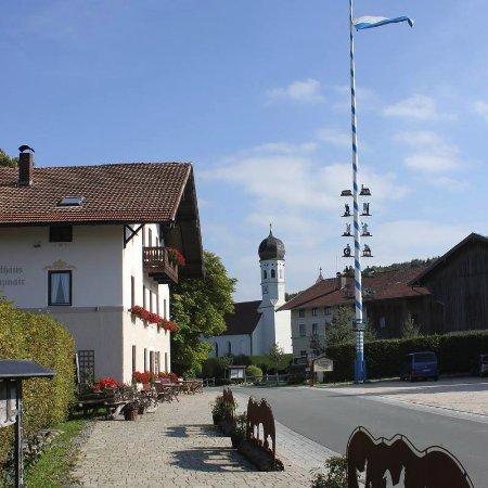 Weyarn, Duitsland: Gasthaus Kreuzmair mit Maibaum und Holzollinger Filialkirche St. Martin