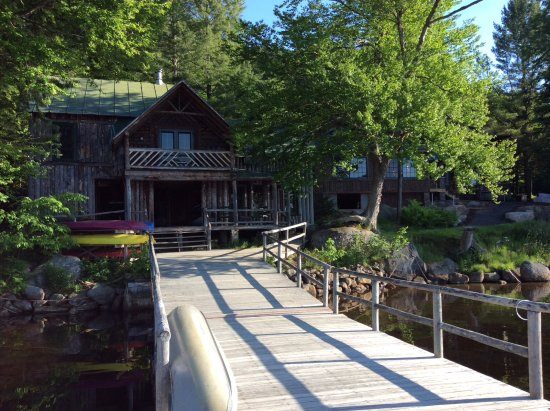 Eagle Bay, estado de Nueva York: View from end of dock looking at canoe storage area, office, and 2nd floor library.