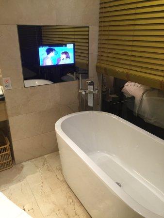 Fuyang, Kina: Chambre et salle de bain avec baignoire et tv