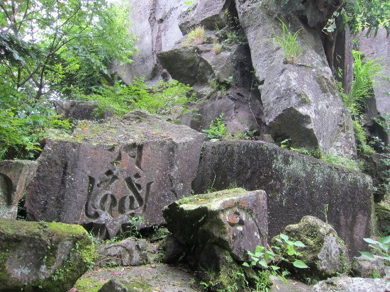 Curved Sanskrit Characters Group on the Polished Cliff in Aoki