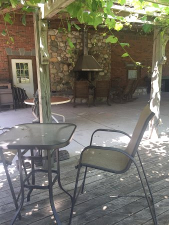 Sans-Souci Euro Inn and Cottages: Rocking chairs around the outdoor fireplace under the grape arbor.