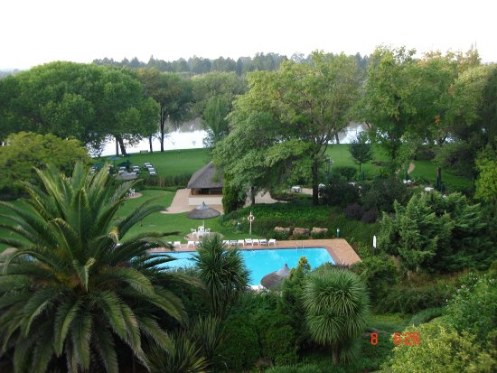 Riverside Sun: looking from the hotel towards the river, seeing the gardens and swimming pool with the river be