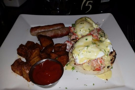 Lobster Benedict with seasoned potatoes and link sausage.