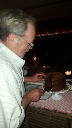 Bovina Center, NY: Gary cutting chocolate layer cake for dessert.
