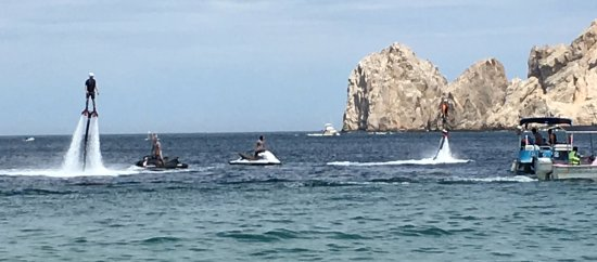 Cabo FlyBoard : Two of us flying. Instructors on jet skis. Blue boat for onlookers/waiting riders.