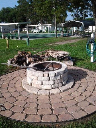 Eustis, FL: Community fire pit with firewood stacked next to it.