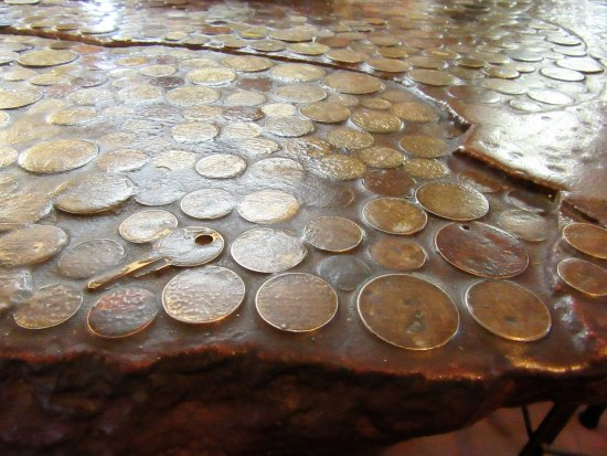 "Terytorium Północne, Australia: A varnished table with coins at ""spud Murphy's hotel"