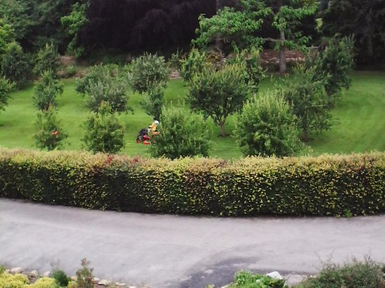 Brympton, UK: Two ride-on mowers noisily being 'driven' around outside the room at 8.30am