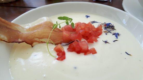 Zgorzelec, Polonia: Käsesuppe mit frischen Tomaten und Chips aus gereiftem Schinken