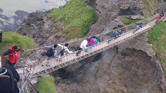Ballintoy, UK: People travelling across the rope bridge.