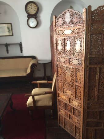 El Hostal de Su Merced: A beautiful piece of wooden furniture in the computer room near the main front desk