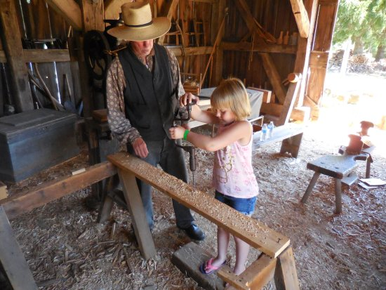 Eagle, WI: my granddaughter using a brace and bit in the carpenter's shop