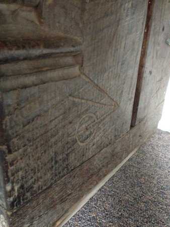 """Suffolk, UK : The artist's """"mark"""" on the pew."""