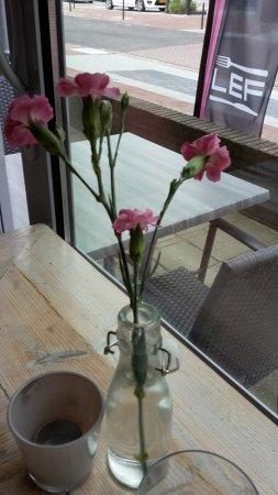 Elst, Nederland: fresh flowes on every table; sign outside