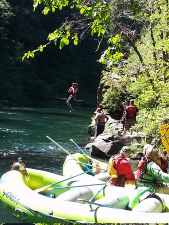 Oregon Whitewater Adventures: Rafter in background has jumped off rock towards water