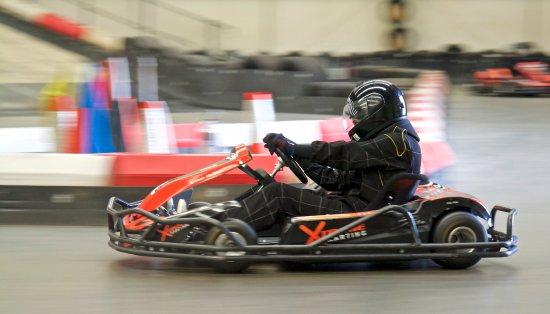 Xtreme Karting Falkirk: Standard kart taking a corner! Overall and helmets standard.