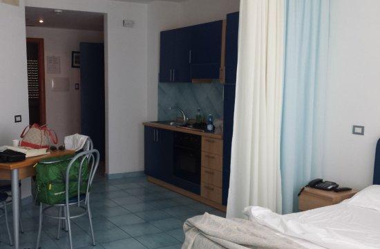 Panorama Santa Tecla Residence: camera e angolo cottura (frigo dietro la tenda del letto) con disimpegno e bagno