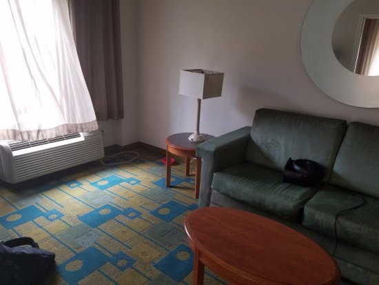 La Quinta Inn & Suites Orlando Convention Center: The living room with a filthy couch and an air intake pulling in smoke from the people at the po