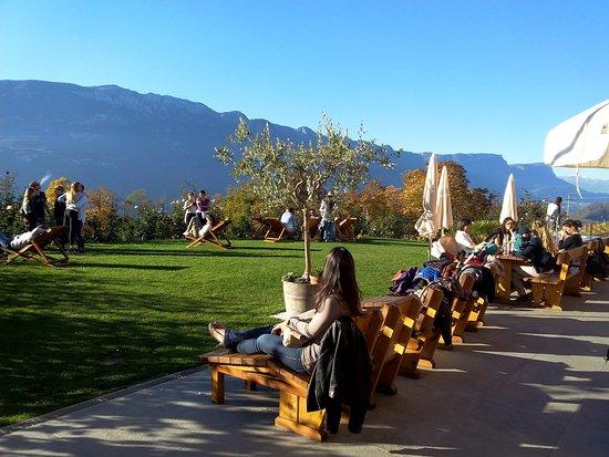 Montagna, Italia: Terrasse und Garten mit Esstischen und Liegestühlen