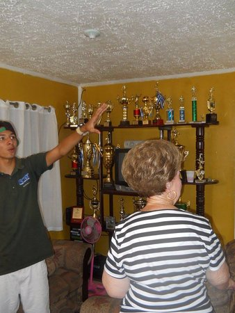 Coxen Hole, Honduras: Joshua showing the soccer trophies in his house - the tour company sponsors local children to pl