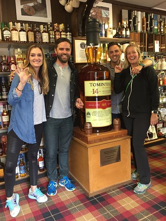 Tomintoul, UK: The best travel crew ever posing next to the largest bottle of Scotch in the world.