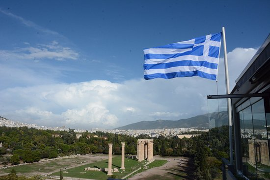 Proud Greek Flag view from rooftop restaurant toward Temple of Olympian Zeus