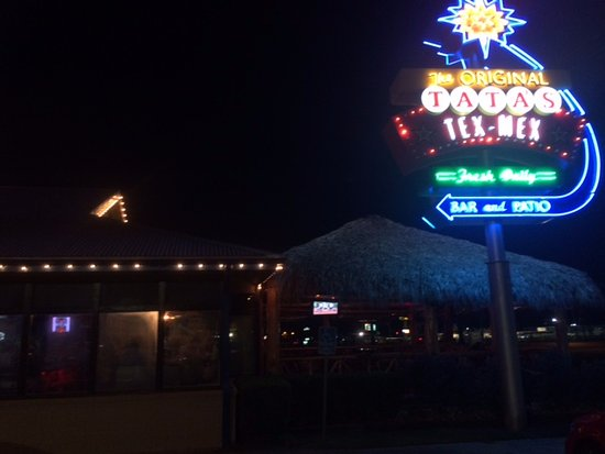 Crockett, TX: sparkle sign with outdoor seating under palapa on right