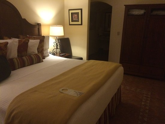 Queen sized bed in the room at Los Arboles Hotel