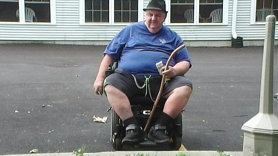 Essex, VT: me in wheel chair outsde smoking area[parking lot]