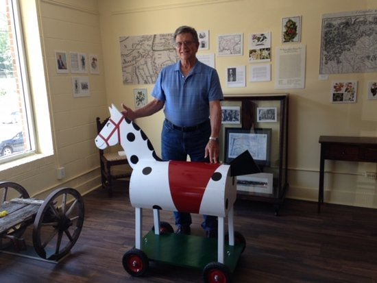 museum volunteer with replica of Tryon's mascot, Morris the toy horse.