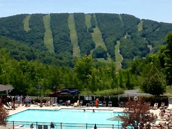 Vacation Village in the Berkshires: View from indoor pool area looking down at the outdoor pool and Jiminy Peak in the distance