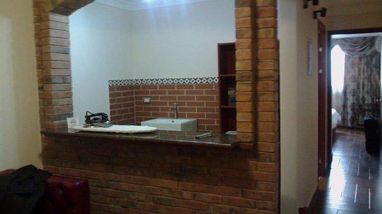 El Doral Apart Hotel: entrada a la habitación, a la izq. hay un sillón y lámpara, enfrente escritorio y silla