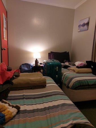YHA Lake Tekapo: 兩張單人床交錯放, 可以在床邊收拾行李, 房內有一個對外窗, 可拉窗簾, 暖氣在中間的屋頂上