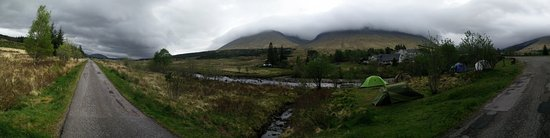 view from across the river onto bridge of orchy and its surrounding mountains