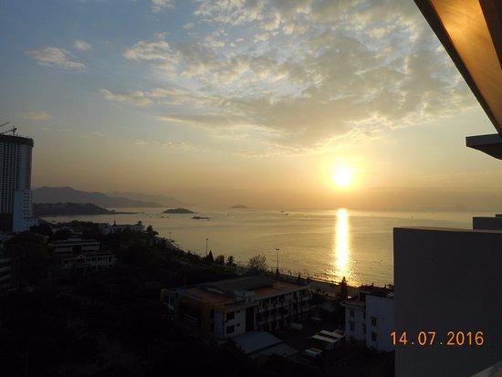 Michelia Hotel : Восход солнца - вид на море и город с балкона номера на 11-м этаже
