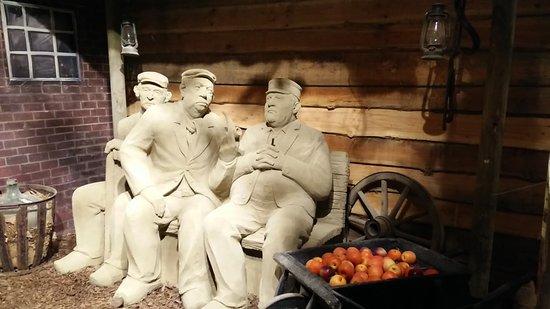 """Garderen, Hollanda: Zandsculptuur: Drie mannen op het """"leugenbankje"""""""