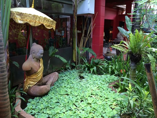 Golden Temple Villa: The lush front yard of the hotel. This is a statue of the great King Jayavarman VII.