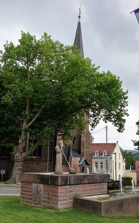 "Quierschieds Kirche mit dem Glasbläserdenkmal ""WAMBES"" davor"