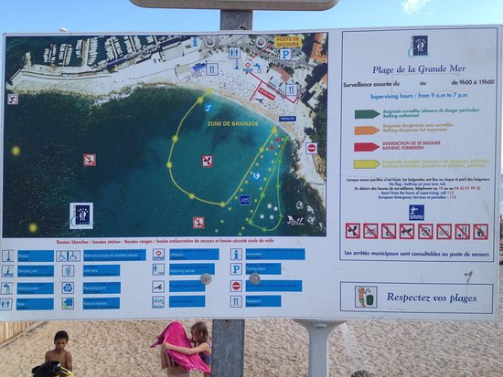 An info board on the beach showing the swimming area and rules
