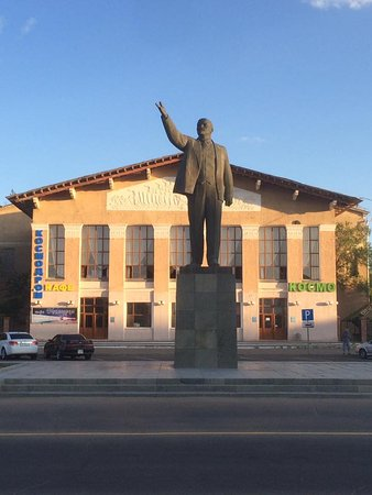 Baikonur, Kazakhstan: Statue of Lenin on the square outside. Shop behind the statue on the right sells bottled water.