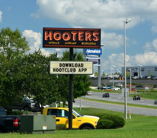 Hooters girls pose in front of restaurant picture of Charlotte motor speedway hotels nearby