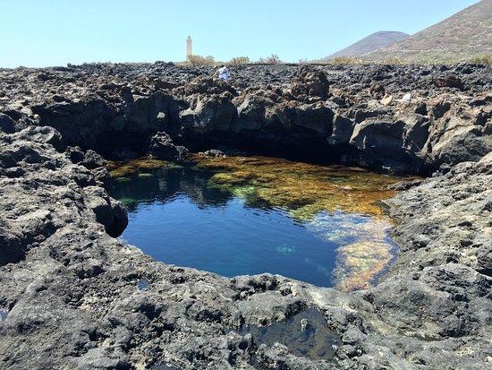 Piscina Naturale: Ecco la piscina come ti appare tra le rocce, con sfondo sul faro