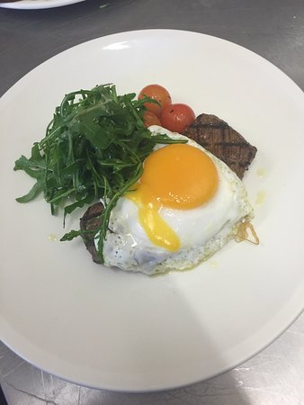 Char grilled rump steak with duck fried egg roast cherry tomatoes rocket salad served chip