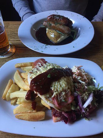 Liss, UK : Chicken, cheese & bacon melt, bbq sauce, salad, coleslaw and chips (bottom), bangers and mash (t
