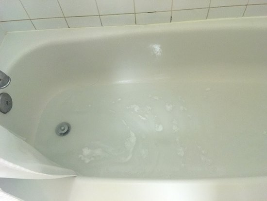 Explorer Hotel: up to 2 inches of water standing in tub after shower due to poor drainage.