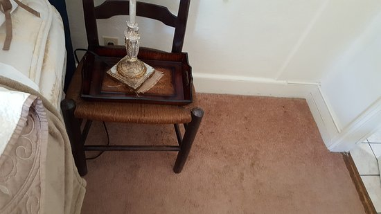 "Lambertville, Nueva Jersey: Stained carpeting, next to ""nightstand""."
