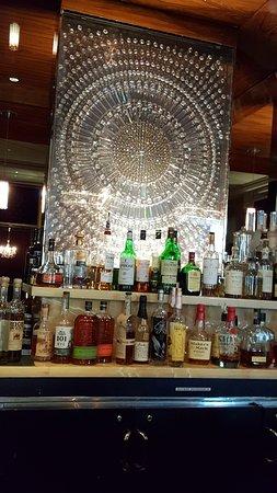 Trump International Hotel Las Vegas: Elegance of a circular, crystal wall display behind numerous liquor bottles in the DJT Bar