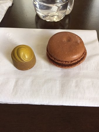 Christophe Artisan Chocolatier - Patissier: Chocolate with caramel from the painted collection sitting beside a chocolate macaroon